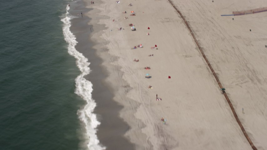 5K stock footage aerial video flying over sunbathers at Rockaway Beach, Queens, New York Aerial Stock Footage | AX71_034