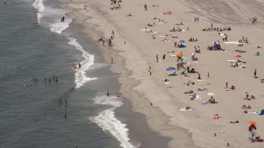 5K stock footage aerial video flying over people in the water at Rockaway Beach, Queens, New York Aerial Stock Footage | AX71_036