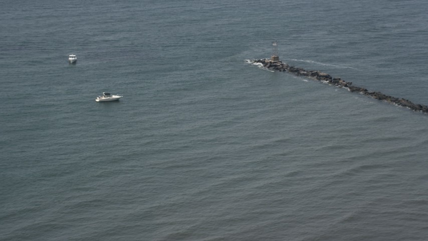 5k aerial video of fishing boats by end of a breakwater in for New york state fishing license online