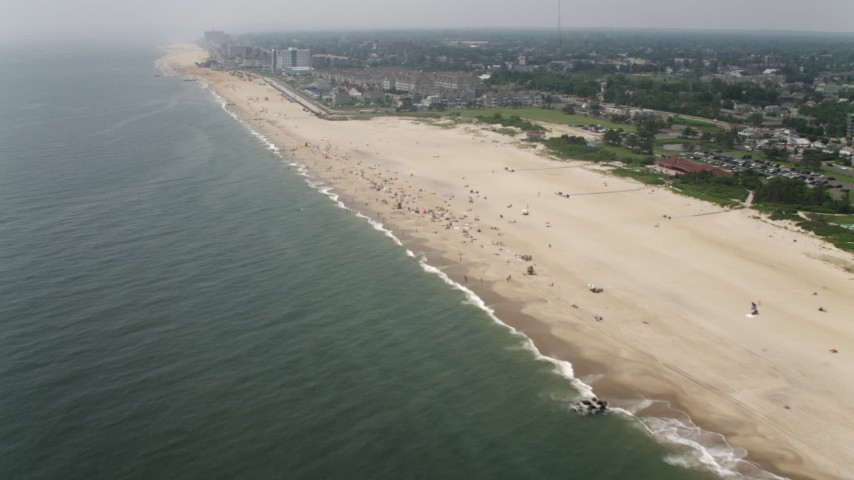 5K stock footage aerial video flying by beachgoers, beach clubs, and condominium complex in Long Branch, Jersey Shore, New Jersey Aerial Stock Footage | AX71_057