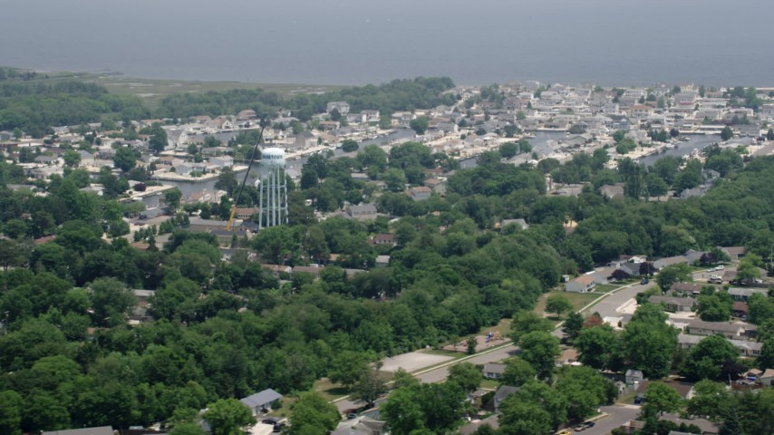 5K stock footage aerial video of homes and water tower by canals in Waretown, New Jersey Aerial Stock Footage | AX71_130