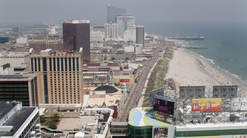 5K aerial video following the boardwalk past hotels in Atlantic City to approach Steel Pier, New Jersey Aerial Stock Footage | AX71_187