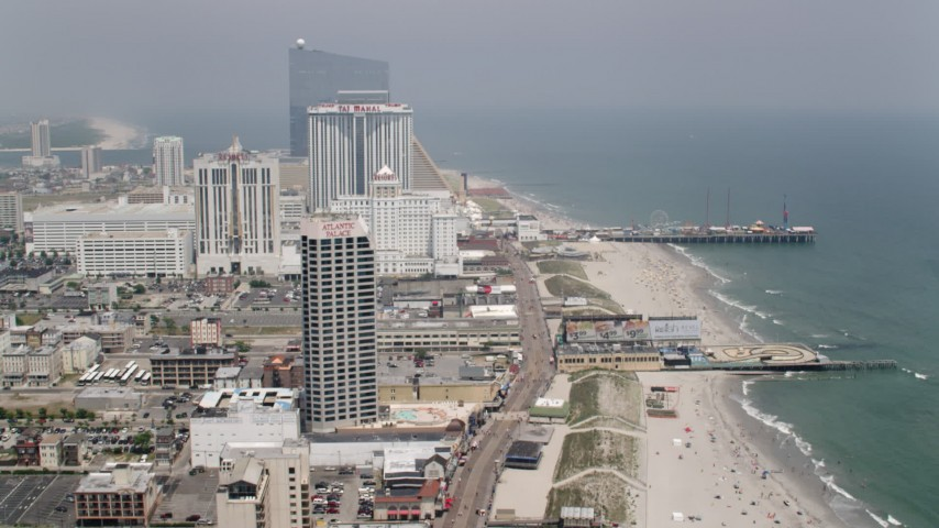 5K aerial video flying over boardwalk past hotels in Atlantic City toward Steel Pier, New Jersey Aerial Stock Footage | AX71_188