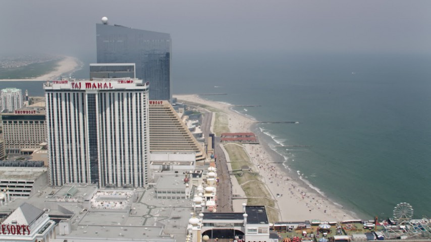 5K stock footage aerial video of Trump Taj Mahal by the boardwalk and beach in Atlantic City, New Jersey Aerial Stock Footage | AX71_189