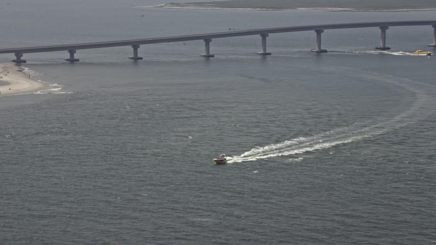 5K aerial video of a fishing boat speeding across Great Egg Harbor Inlet near Ocean Drive Bridge, Ocean City, New Jersey Aerial Stock Footage | AX71_216