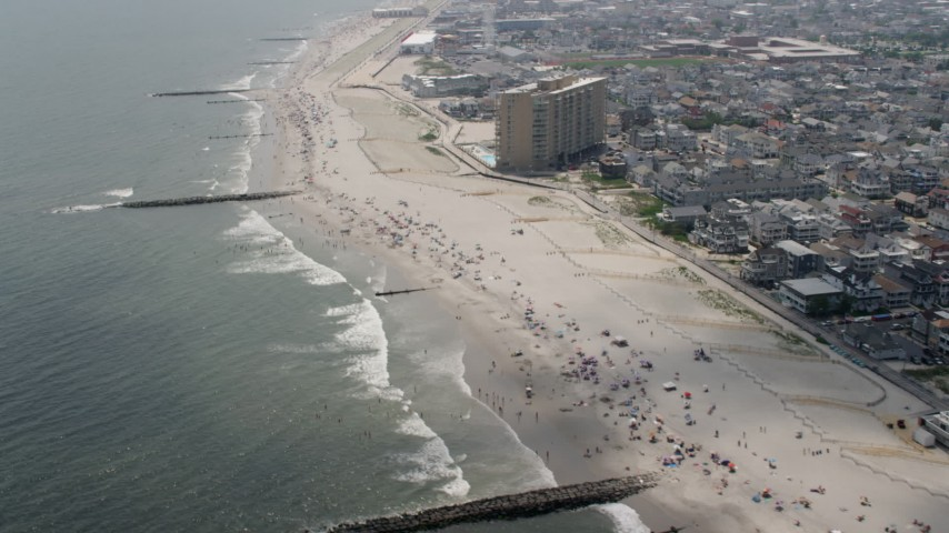 Beach goers on the beach near homes and condo complex in Ocean City, New Jersey Aerial Stock Footage | AX71_218