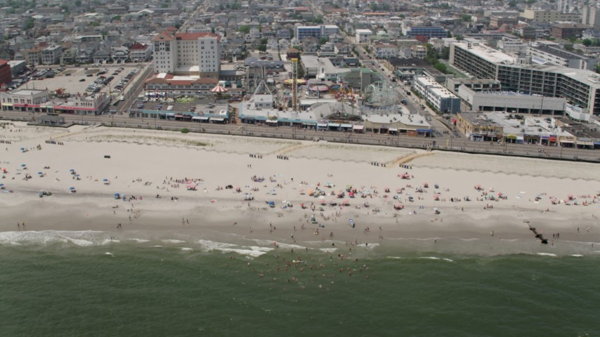 Sunbathers on the beach by Playland's Castaway Cove, Ocean City, New Jersey Aerial Stock Footage | AX71_222