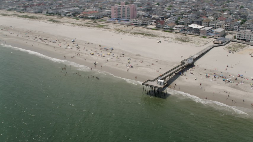 A pier and a populated beach in Ocean City, New Jersey Aerial Stock Footage | AX71_223