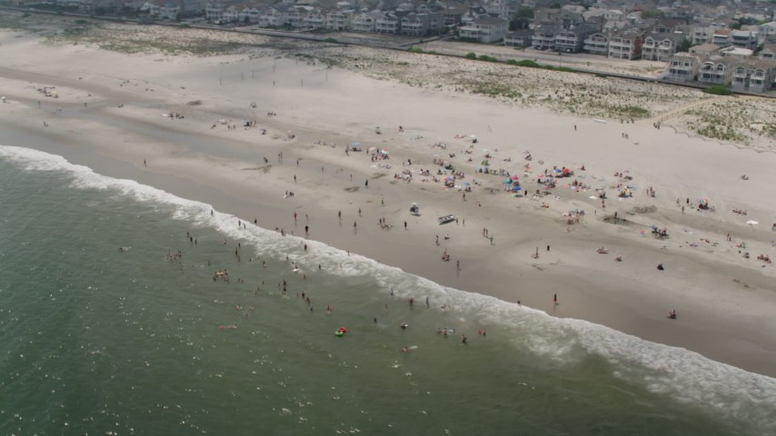 People on the beach in Ocean City, New Jersey Aerial Stock Footage | AX71_224