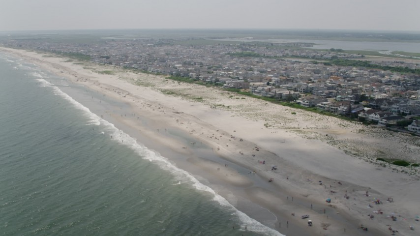 People on the beach and beachfront homes in Ocean City, New Jersey Aerial Stock Footage | AX71_225