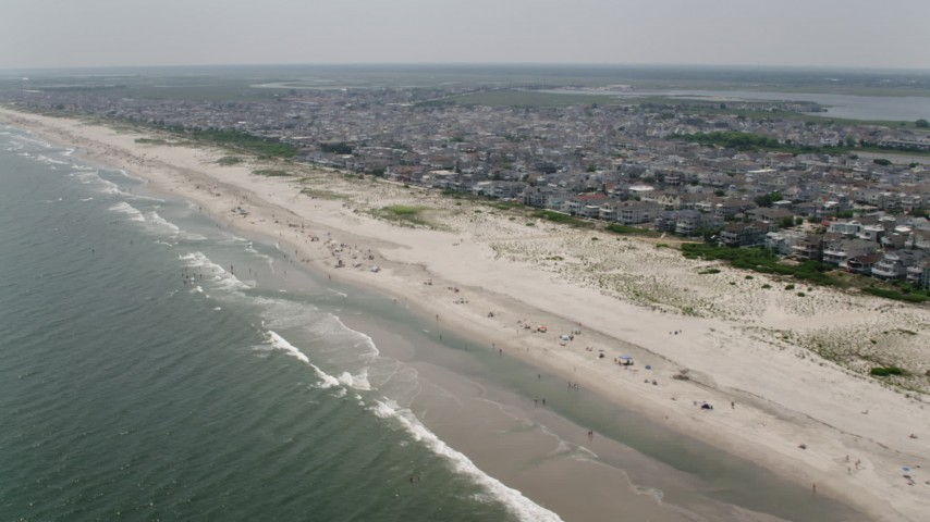 Beach goers and beachfront neighborhoods in Ocean City, New Jersey Aerial Stock Footage | AX71_226
