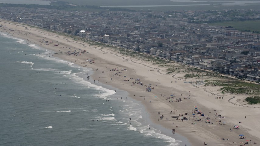 A populated beach and beachfront neighborhoods in Ocean City, New Jersey Aerial Stock Footage | AX71_228