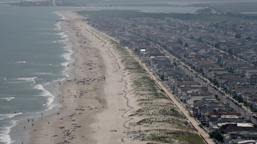 Flyby beach goers and beachfront neighborhoods in Ocean City, New Jersey Aerial Stock Footage | AX71_229