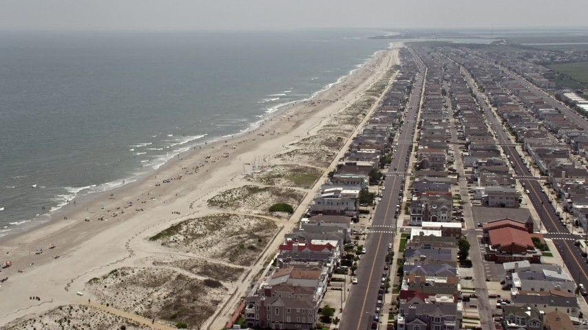Sunbathers on the beach and oceanfront homes in Ocean City, New Jersey Aerial Stock Footage   AX71_230