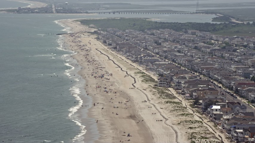 Sunbathers enjoying the beach near oceanfront homes in Ocean City, New Jersey Aerial Stock Footage | AX71_231