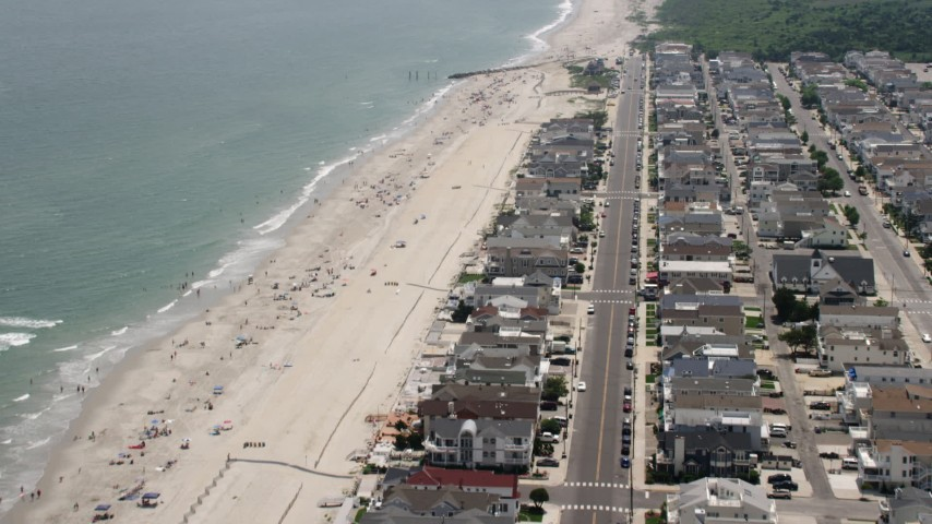 5K aerial video flying over beachfront homes and tilt to sunbathers on the beach in Ocean City, New Jersey Aerial Stock Footage | AX71_233