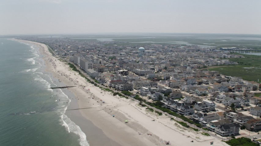 5K stock footage aerial video of sunbathers and beachfront apartment buildings in Sea Isle City, New Jersey Aerial Stock Footage | AX71_240