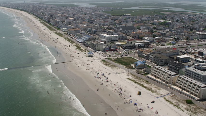 5K stock footage aerial video of sunbathers and Sea Isle City Promenade, New Jersey Aerial Stock Footage AX71_241 | Axiom Images