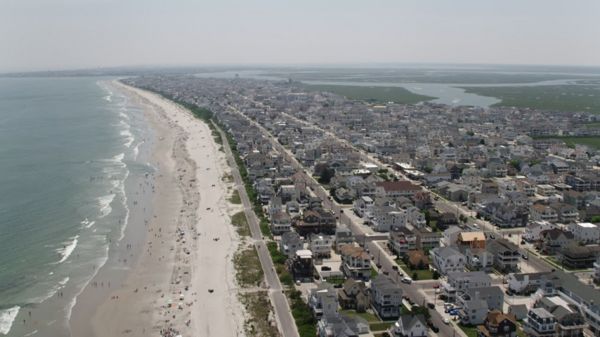 5K stock footage aerial video flying over a populated beach and beachfront homes in Sea Isle City, New Jersey Aerial Stock Footage | AX71_242