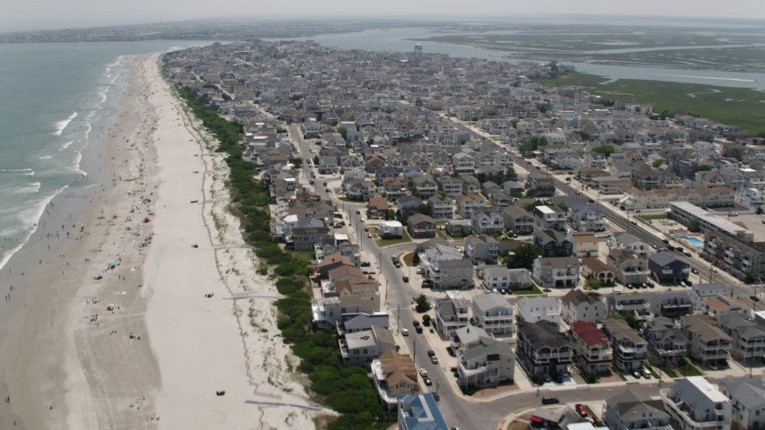 5K stock footage aerial video of beach goers and beachfront neighborhoods in Sea Isle City, New Jersey Aerial Stock Footage | AX71_244