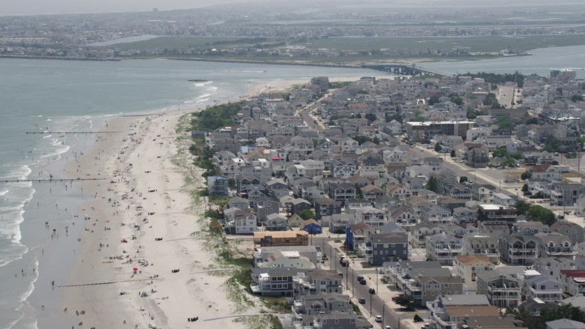 5K stock footage aerial video flying over beach goers by beachfront homes near Townsends Inlet Bridge in Sea Isle City, New Jersey Aerial Stock Footage | AX71_245