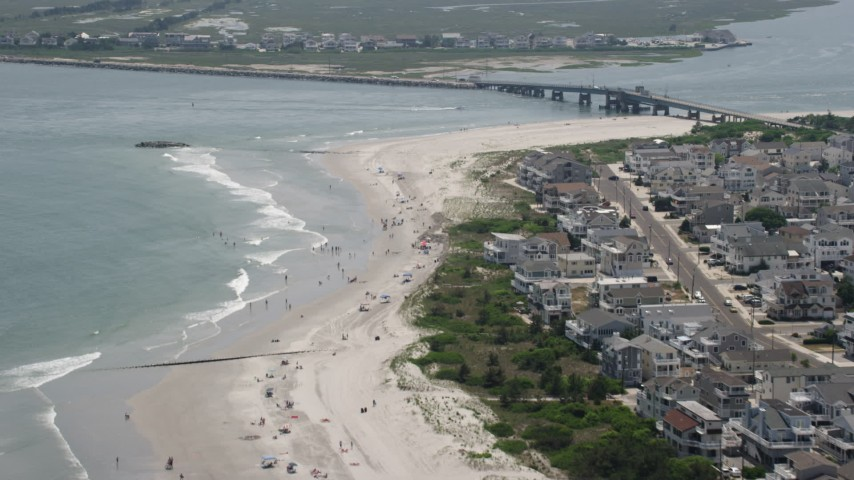 5K stock footage aerial video of beach goers near Townsends Inlet Bridge in Sea Isle City, New Jersey Aerial Stock Footage | AX71_246