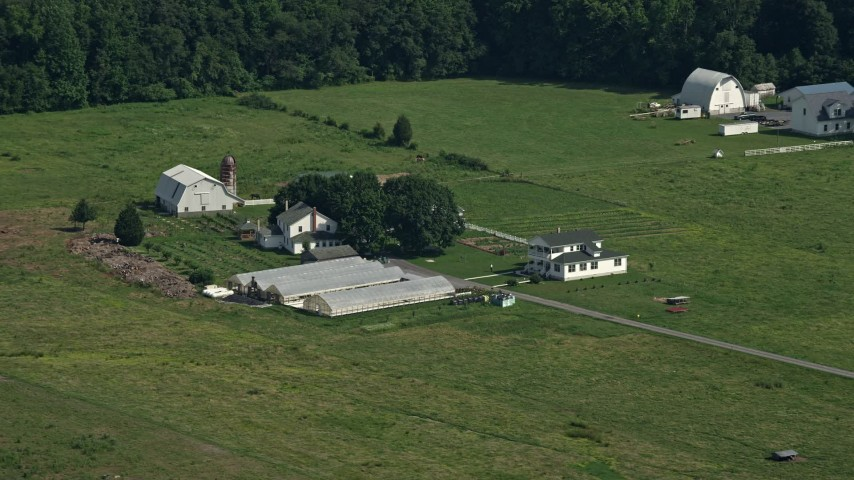5K stock footage aerial video of a farmhouse, barns, and greenhouses in Dover, Delaware Aerial Stock Footage | AX72_086