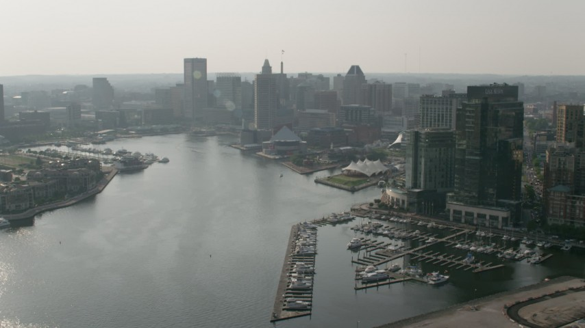 5K aerial video of National Aquarium and Inner Harbor Piers, Downtown Baltimore skyscrapers, Maryland Aerial Stock Footage | AX73_067