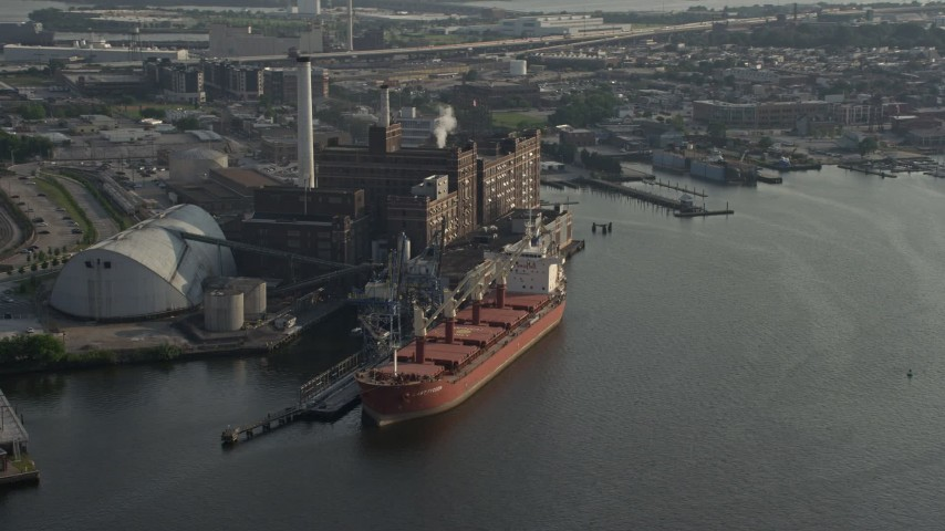 5K stock footage aerial video of a cargo ship docked by the Domino Sugar Factory, Baltimore, Maryland Aerial Stock Footage | AX73_101