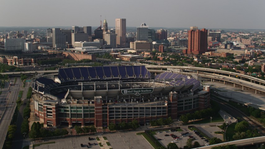 5K aerial video orbiting M&T Bank Stadium with Downtown Baltimore skyscrapers in the background, Maryland Aerial Stock Footage | AX73_114