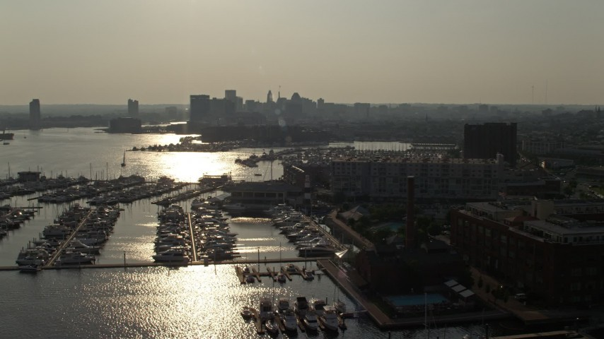 5K stock footage aerial video of boats docked at the Baltimore Marine Center by riverfront office buildings, Maryland Aerial Stock Footage | AX73_145