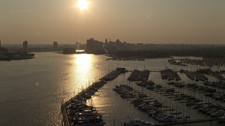 5K stock footage aerial video flying over Baltimore Marine Center to approach Downtown Baltimore skyline at sunset, Maryland Aerial Stock Footage | AX73_148