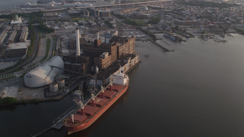 5K aerial video of cargo ship docked at the Domino Sugar Factory by the Patapsco River at sunset in Baltimore, Maryland Aerial Stock Footage | AX73_151