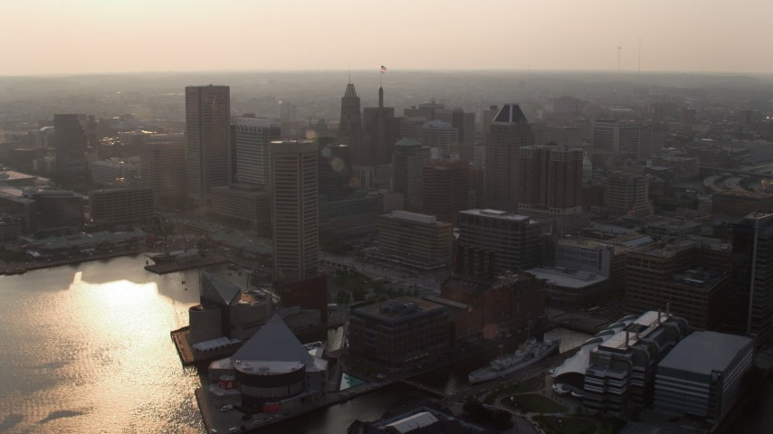 5K aerial video approaching Downtown Baltimore skyscrapers by Inner Harbor and piers at sunset, Maryland Aerial Stock Footage | AX73_152