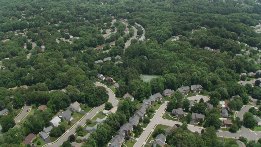 5K aerial video flying over suburban homes and green trees in Fairfax, Virginia Aerial Stock Footage | AX74_012