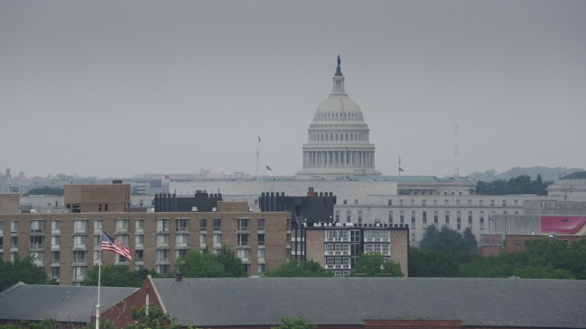 5K stock footage aerial video of the United States Capitol Dome seen from apartment buildings in Washington DC Aerial Stock Footage | AX74_064