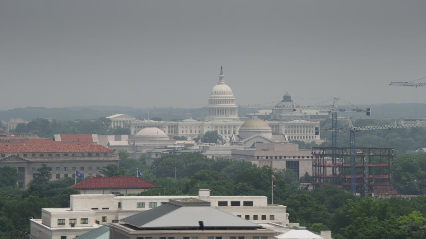 5K stock footage aerial video of the United States Capitol seen over Smithsonian Museum domes in Washington DC Aerial Stock Footage | AX74_077