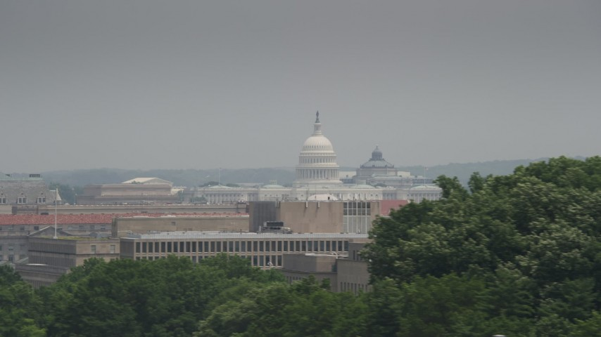 5K stock footage aerial video flying by trees to reveal United States Capitol and a government office building in Washington DC Aerial Stock Footage | AX74_078