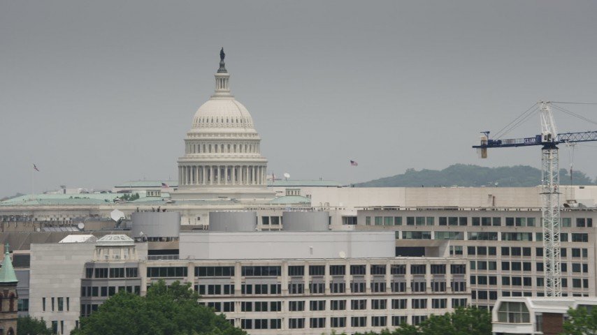 5K stock footage aerial video of United States Capitol Dome seen above office buildings in Washington DC Aerial Stock Footage | AX74_089
