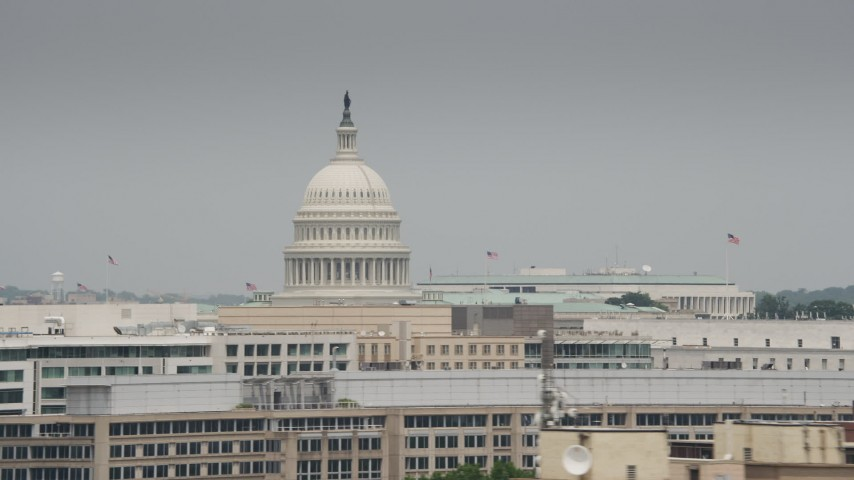 5K stock footage aerial video of the United States Capitol Dome Visible over office buildings rooftops in Washington DC Aerial Stock Footage | AX74_090