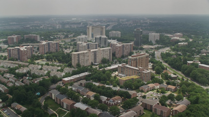 5K aerial video flying over apartment buildings to approach larger complexes in Alexandria, Virginia Aerial Stock Footage | AX74_122
