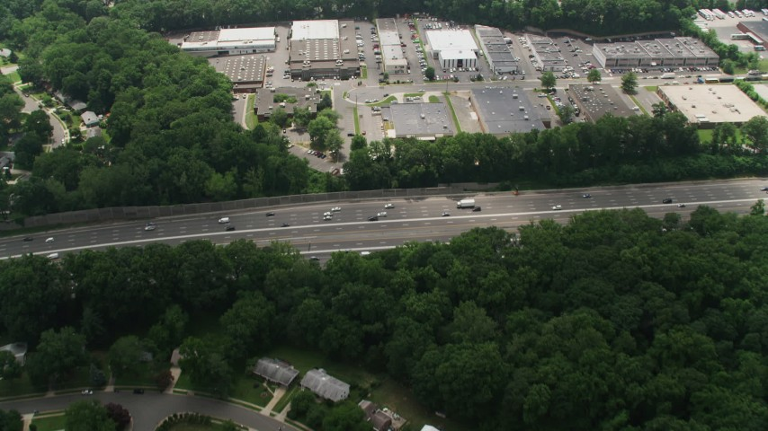 5K stock footage aerial video of a bird's eye view of I-495 and a business park to reveal suburban neighborhoods in Springfield, Virginia Aerial Stock Footage | AX74_132
