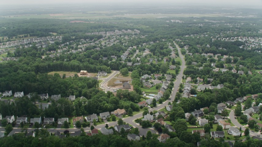 5K stock footage aerial video flying over ponds to approach Prince William County Fairgrounds by suburban homes in Manassas, Virginia Aerial Stock Footage | AX74_150