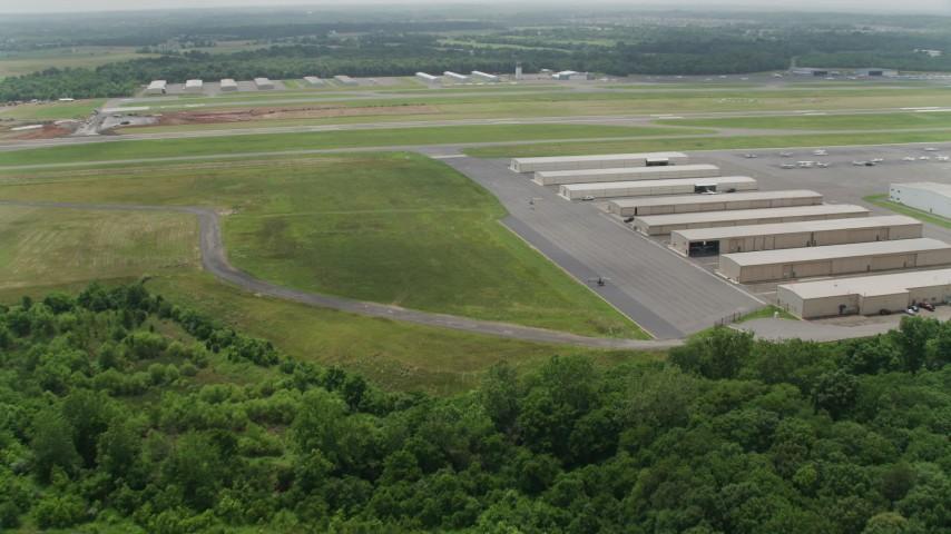 5K stock footage aerial video approaching hangars and runway at Manassas Regional Airport, Virginia Aerial Stock Footage | AX74_153