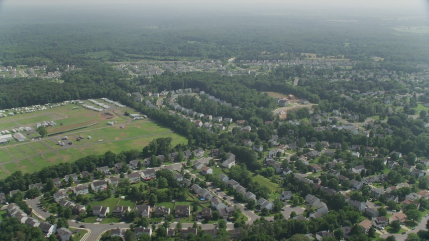 5K stock footage aerial video flying by neighborhoods in Manassas, Virginia to reveal Prince William County Fairgrounds Aerial Stock Footage | AX75_002