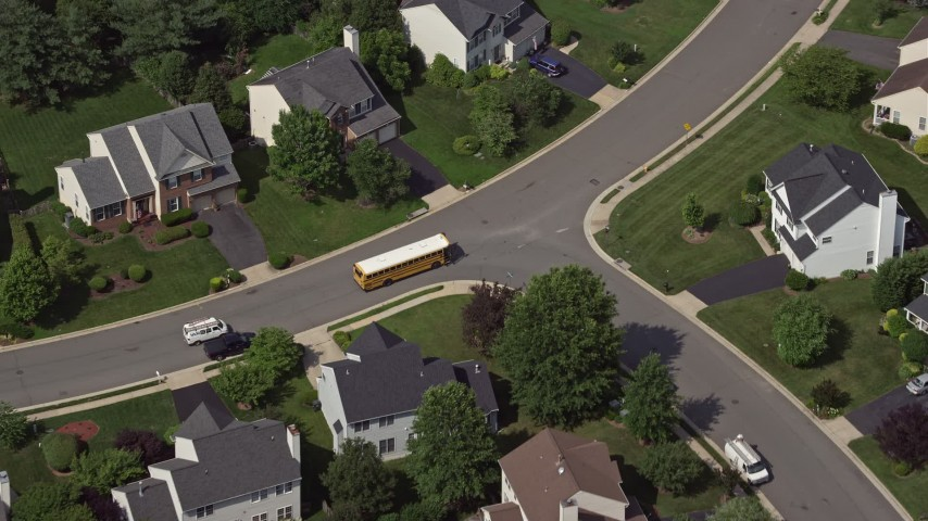 5K stock footage aerial video tracking a school bus in a suburban neighborhood in Manassas, Virginia Aerial Stock Footage | AX75_004