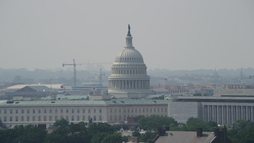 5K stock footage aerial video of the United States Capitol dome behind Cannon House Offices and James Madison Building in Washington DC Aerial Stock Footage | AX75_056