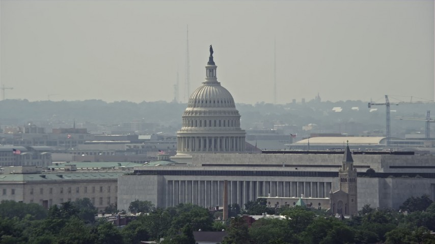 5K stock footage aerial video of the United States Capitol dome behind Cannon House Offices and James Madison Building in Washington DC Aerial Stock Footage   AX75_056E