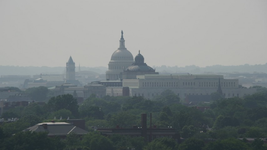 5K aerial video of the domes of the United States Capitol and Thomas Jefferson Building behind the John Adams Building in Washington DC Aerial Stock Footage | AX75_061