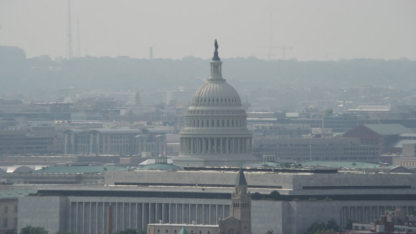 5K stock footage aerial video of the United States Capitol dome behind the James Madison Building in Washington DC Aerial Stock Footage | AX75_069